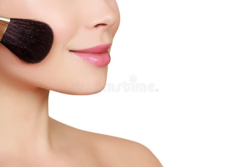 Belle femme faisant le maquillage sur le visage avec la brosse cosmétique photos libres de droits