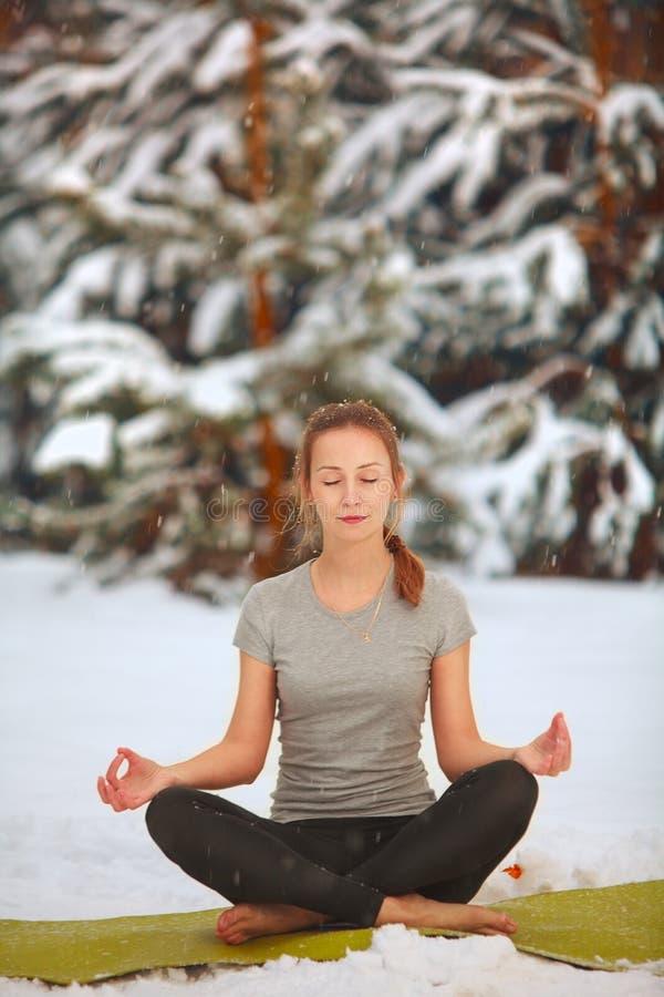 Belle femme faisant le yoga dehors dans la neige images stock