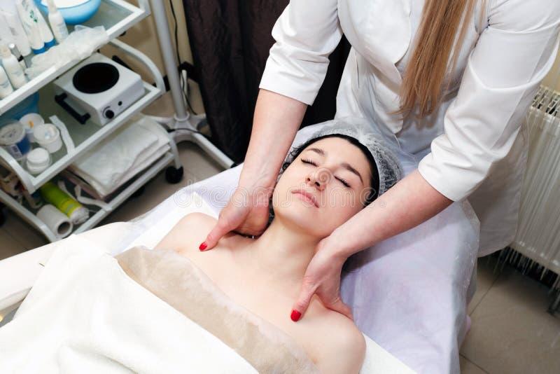 Belle femme faisant un massage du visage dans un salon de spa Soins de beauté du visage, soins de la peau et du corps Vue en angl images stock