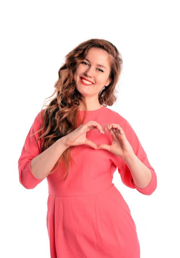 Belle femme faisant une forme de coeur avec ses mains D'isolement sur le blanc image stock