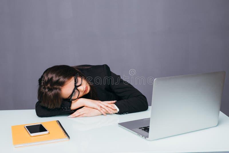 Belle femme fatiguée d'affaires dormant sur son bureau dans son bureau photo stock