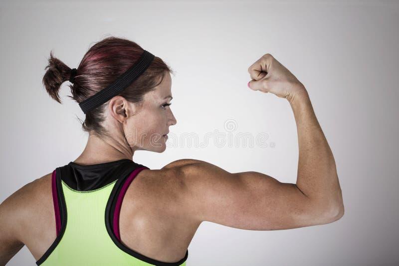 Belle femme forte de forme physique fléchissant son bras et muscles du dos photographie stock