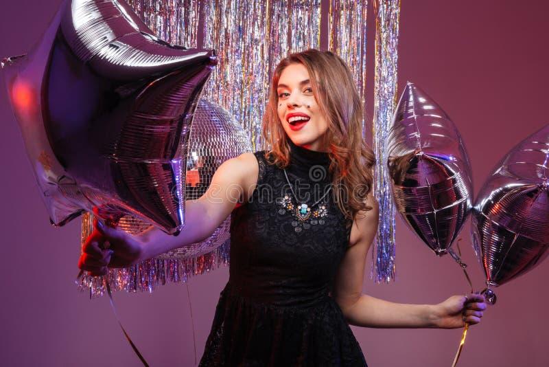 Belle femme gaie tenant les ballons en forme d'étoile image libre de droits