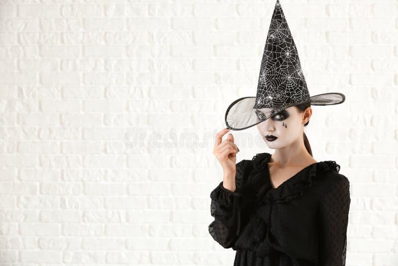 Belle femme habillée comme sorcière pour Halloween sur le fond blanc photos libres de droits