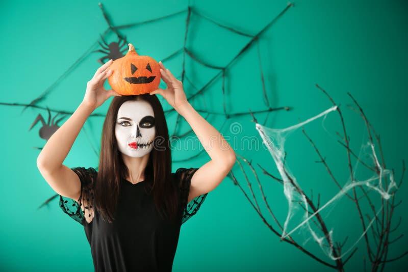Belle femme habillée pour Halloween avec la position de potiron près du mur décoré image stock