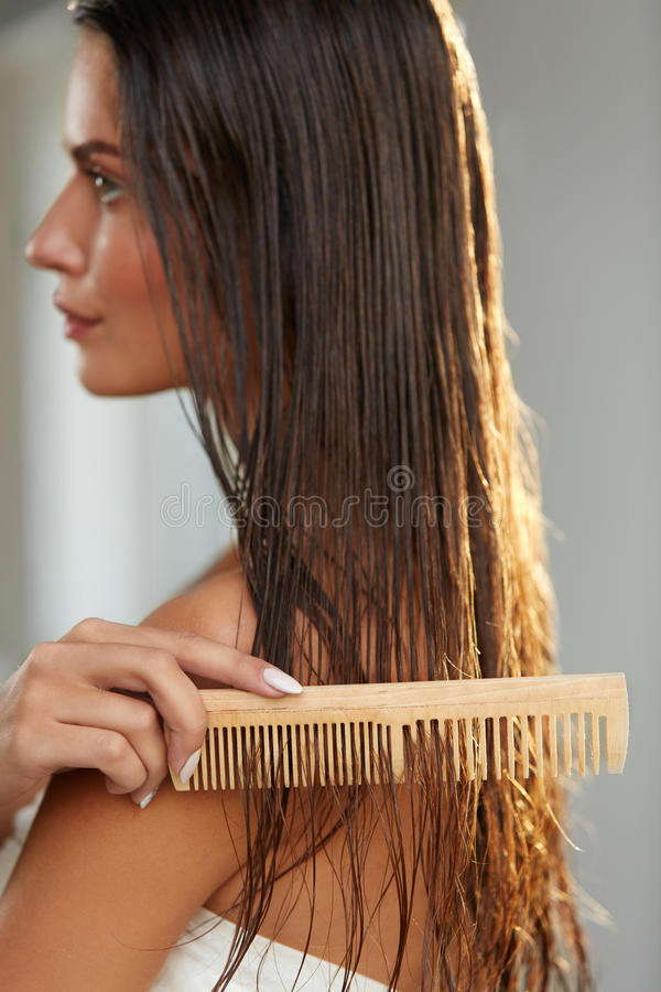 Belle femme Hairbrushing ses longs cheveux humides Soins capillaires photos stock