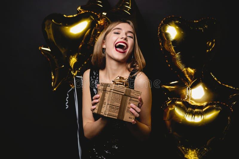 Belle femme heureuse avec le boîte-cadeau à la partie de célébration Anniversaire ou soirée du Nouveau an célébrant le concept photos libres de droits