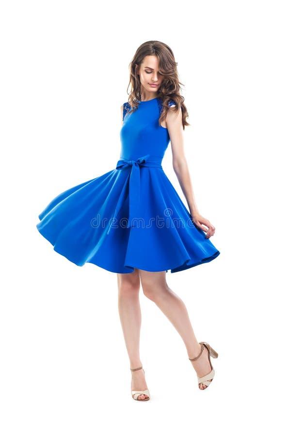 Belle femme heureuse dans la robe bleue posant dans le studio d'isolement dessus image stock