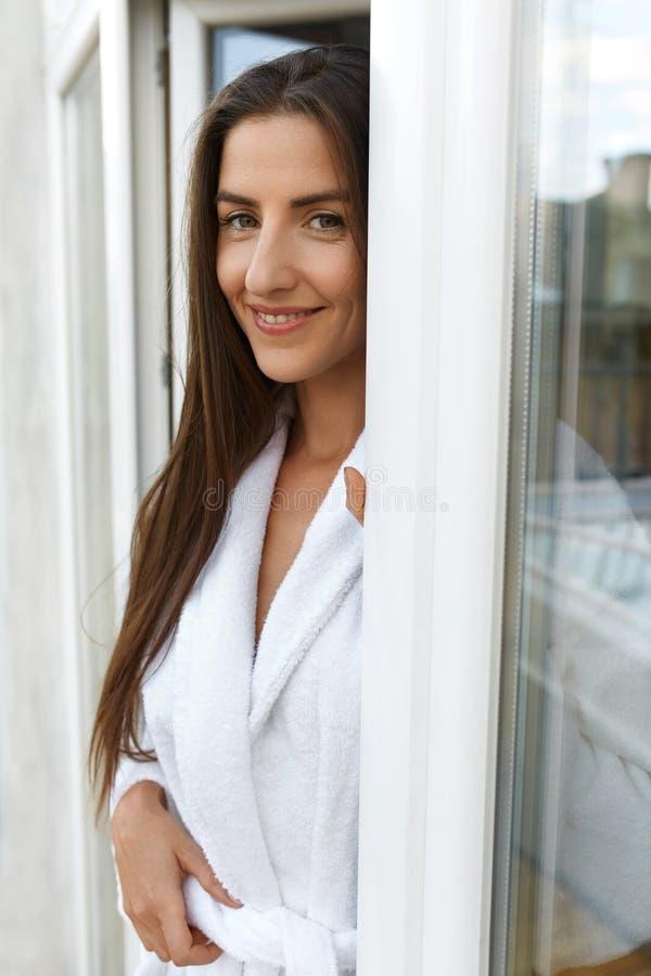 Belle femme heureuse dans le matin à la fenêtre après s'être réveillé images libres de droits