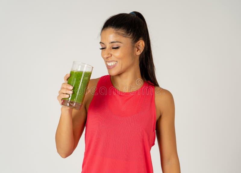 Belle femme heureuse de sport d'ajustement souriant et buvant le smoothie sain de légume frais photographie stock