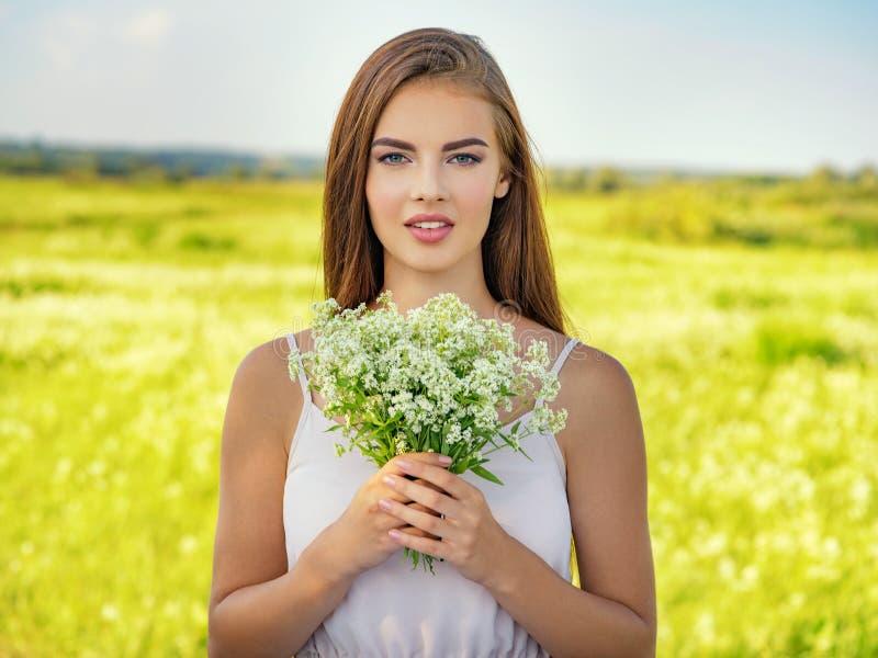 Belle femme heureuse et souriante extérieure avec des fleurs dans des mains photos libres de droits