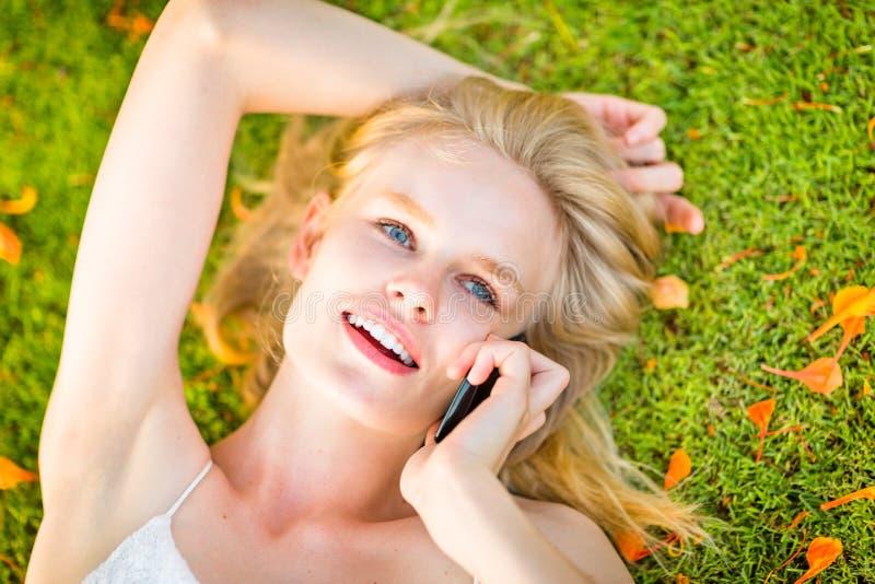 Belle femme heureuse invitant un téléphone portable tout en se trouvant sur l'herbe verte pendant le temps d'automne photos libres de droits