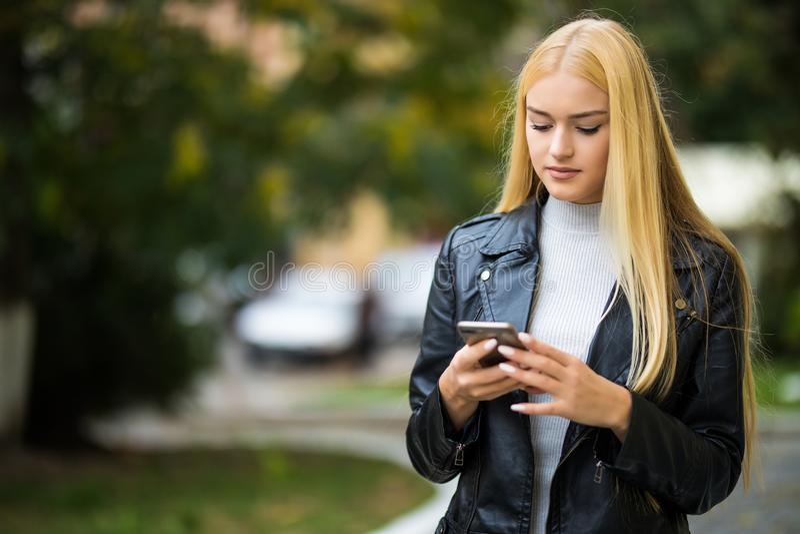 Belle femme heureuse marchant et écrivant ou lisant des messages de sms sur la ligne à un téléphone intelligent tandis que dans u image stock