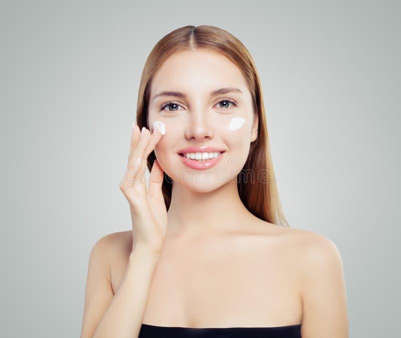 Belle femme heureuse mettant la crème sur la peau saine photographie stock