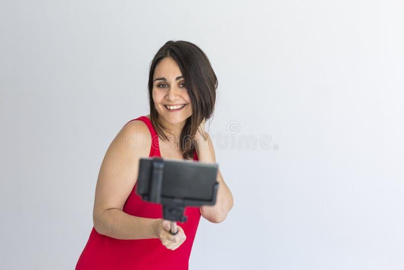 Belle femme heureuse prenant un selfie avec le téléphone intelligent au-dessus du fond blanc lifestyle Vêtements décontractés et  images libres de droits
