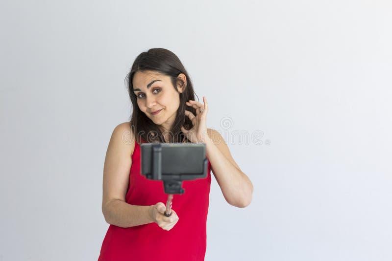 Belle femme heureuse prenant un selfie avec le téléphone intelligent au-dessus du fond blanc lifestyle Vêtements décontractés et  photo libre de droits
