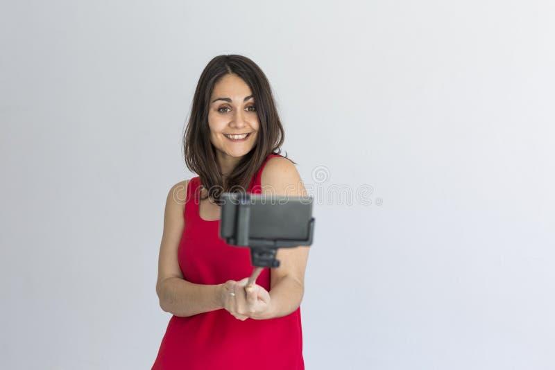 Belle femme heureuse prenant un selfie avec le téléphone intelligent au-dessus du fond blanc lifestyle Vêtements décontractés de  photos stock