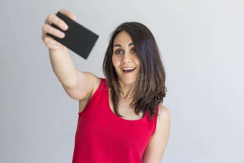 Belle femme heureuse prenant un selfie avec le téléphone intelligent au-dessus du fond blanc lifestyle Vêtements décontractés de  photographie stock