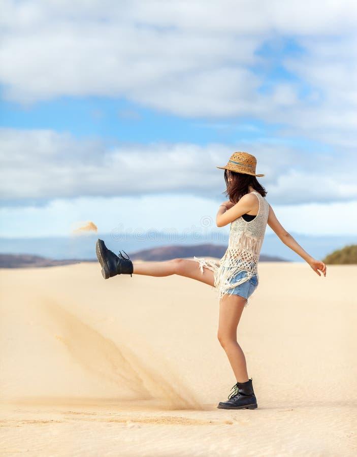 Belle femme hippie donnant un coup de pied le sable et ayant l'amusement dans le désert dessus photos stock