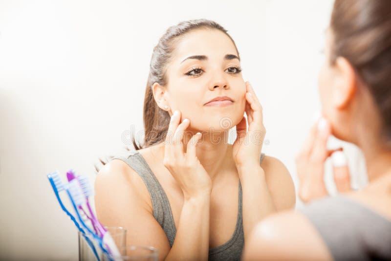 Belle femme hispanique regardant un miroir images libres de droits