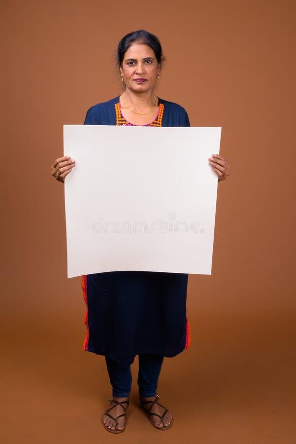 Belle femme indienne mûre tenant le conseil blanc vide avec le copyspace photo stock