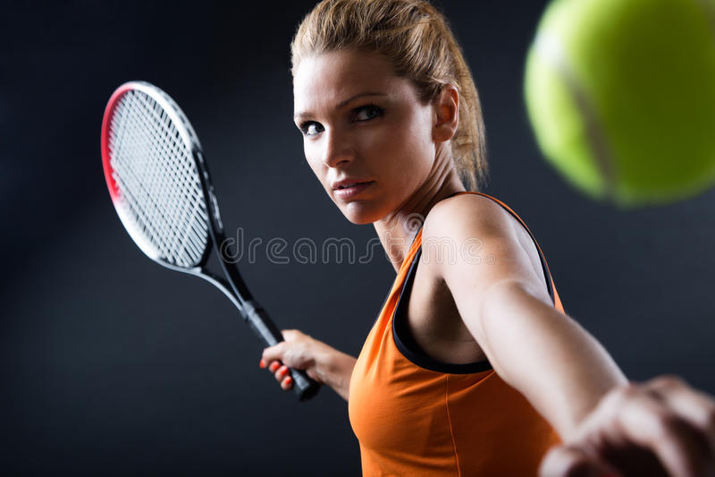 Belle femme jouant le tennis d'intérieur D'isolement sur le noir image libre de droits