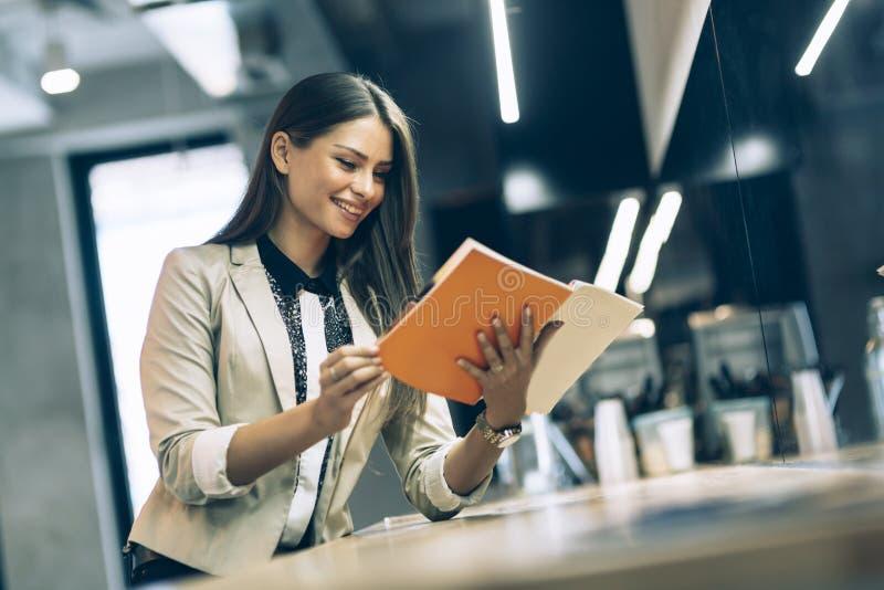 Belle femme lisant le menu sur un compteur photographie stock libre de droits