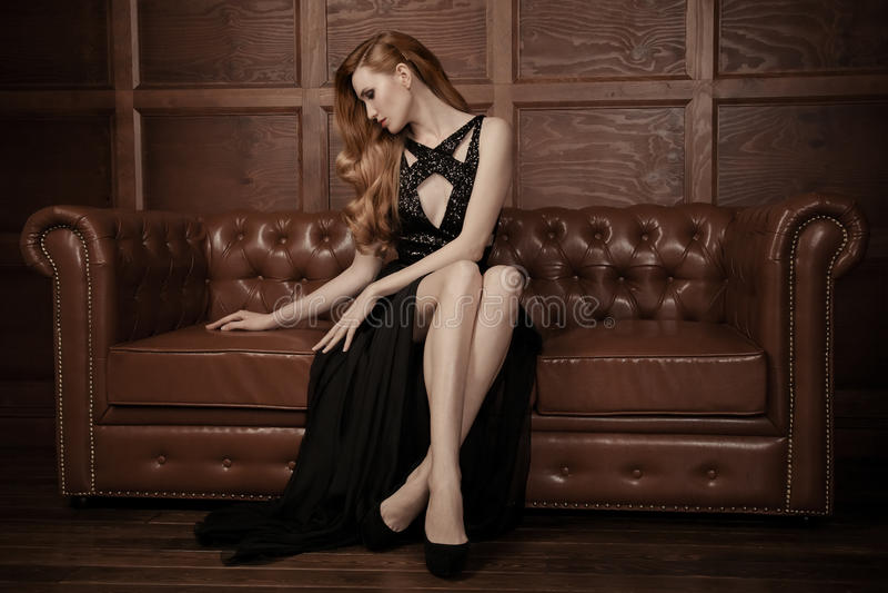 Belle femme luxueuse s'asseyant sur un vi en cuir images stock