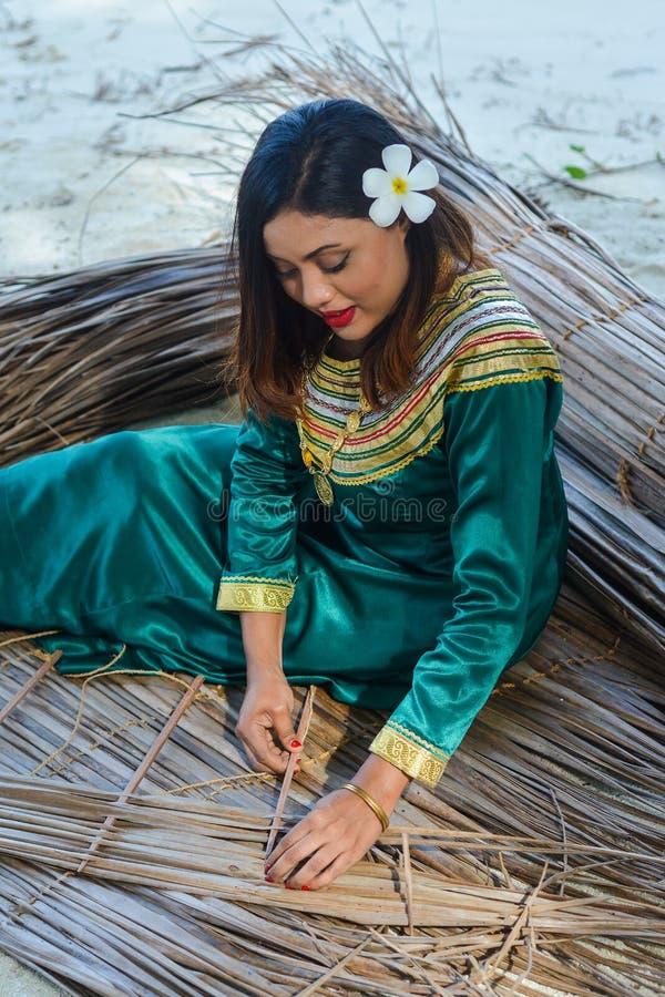 Belle femme maldivienne dans la robe nationale faisant des plats à partir des feuilles sèches photos libres de droits