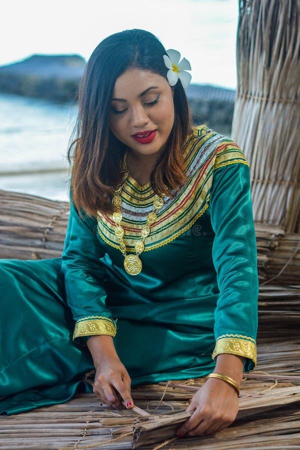 Belle femme maldivienne dans la robe nationale faisant des plats à partir des palmettes sèches images libres de droits