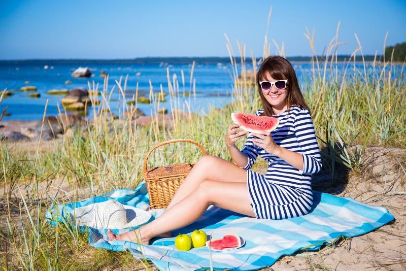 Belle femme mangeant la pastèque sur la plage images stock