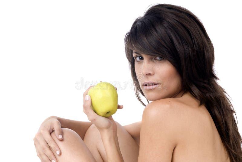 Belle femme mangeant une pomme dans le blanc photographie stock