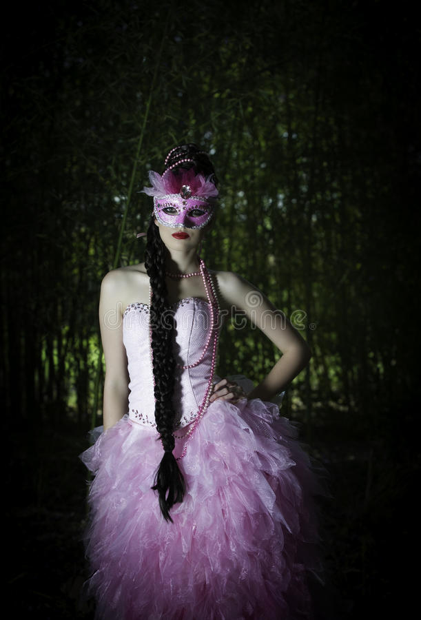 Belle femme masquée avec la coiffure tressée dans la robe de soirée rose se tenant dans une forêt avec sa main sur sa hanche photos libres de droits