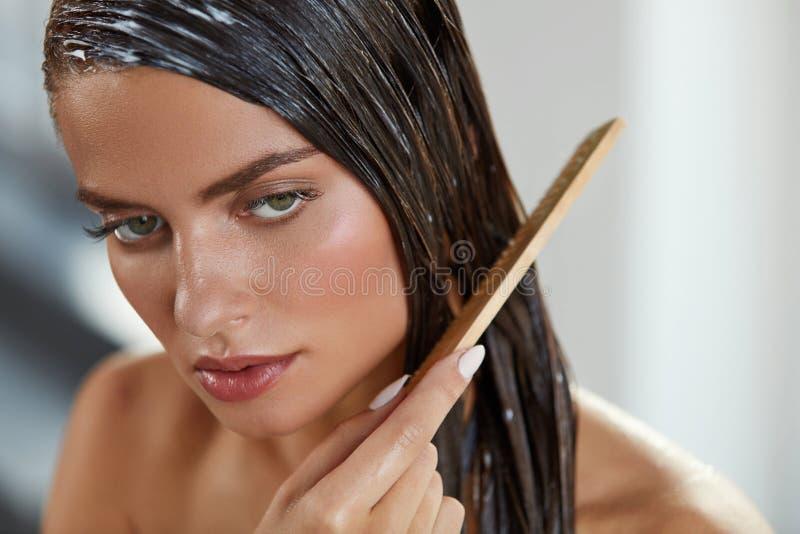 Belle femme mettant le masque sur de longs cheveux humides Hairbrushing image libre de droits