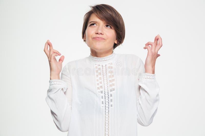 Belle femme mignonne inspirée faisant un souhait avec des doigts croisés photo libre de droits