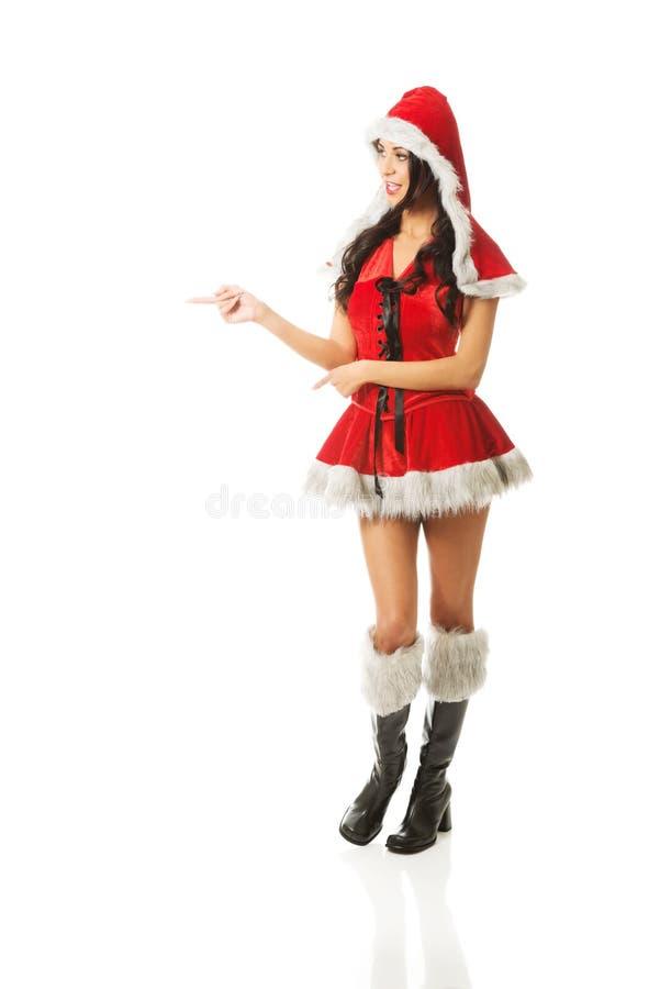 Belle femme mince portant des vêtements de Santa et indiquant la gauche photos stock