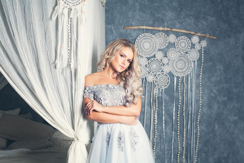 Belle femme modèle dans la robe grise de Tulle détendant dans l'intérieur de cru photo libre de droits