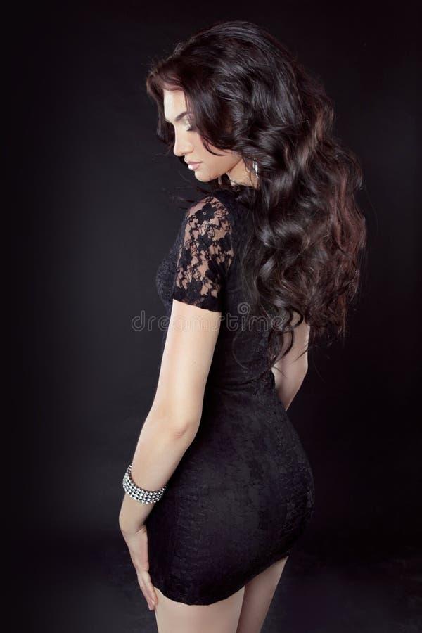 Belle femme modèle de brune avec de longs cheveux bouclés, dans la robe photos libres de droits
