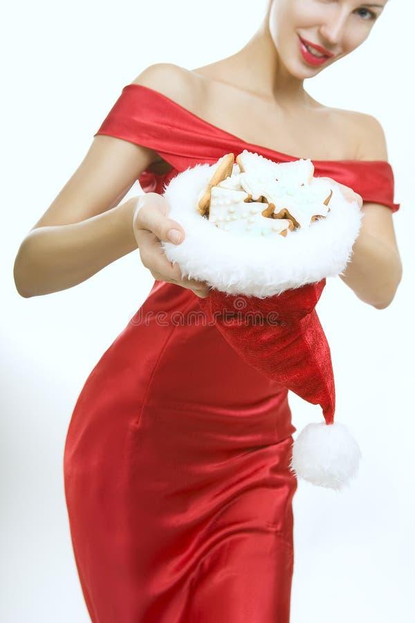 Belle femme montrant le chapeau de Santa Claus avec des biscuits de Noël photos libres de droits