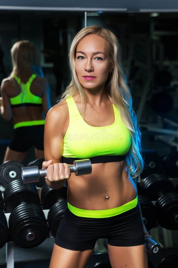 Belle femme musculaire d'ajustement exerçant des muscles de bâtiment photo stock