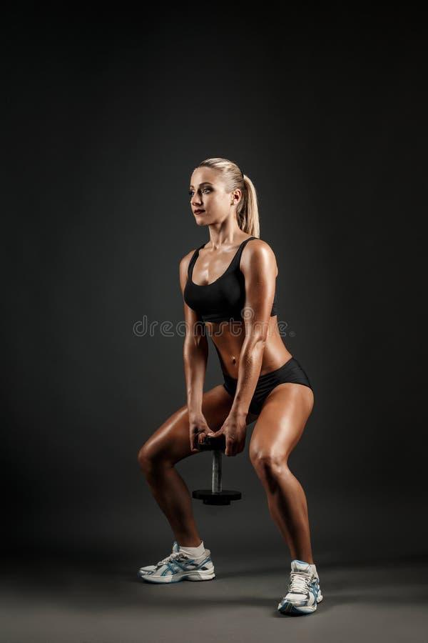 Belle femme musculaire faisant l'exercice de jambe sur un fond gris-foncé dans le studio photos stock