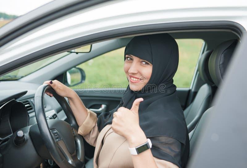 Belle femme musulmane arabe conduisant la voiture et montrant des pouces  image libre de droits