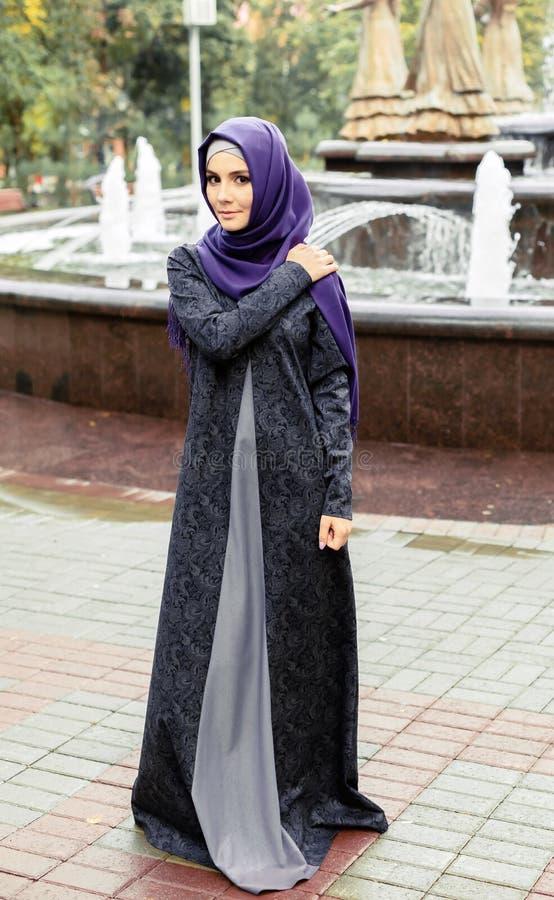 Belle femme musulmane dans la promenade islamique moderne de robe en parc de ville image stock