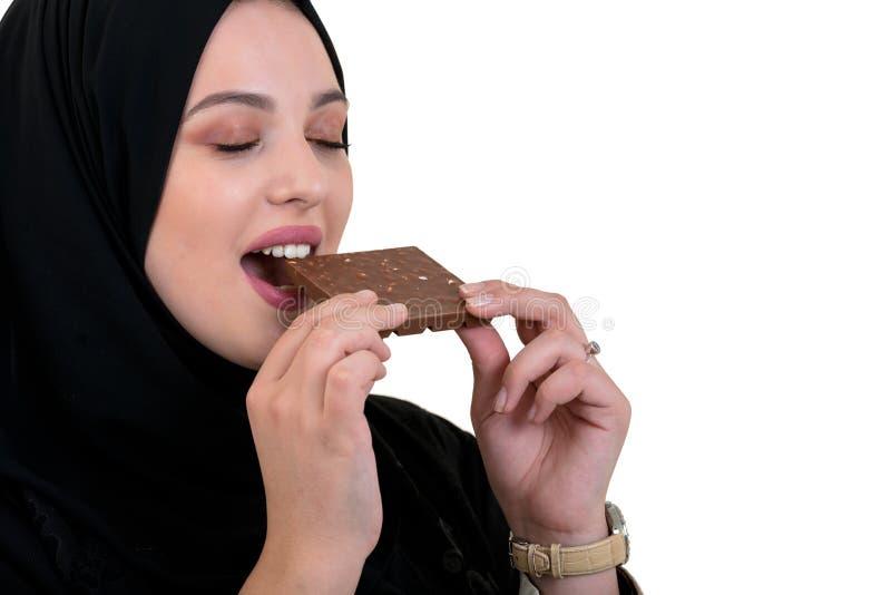 Belle femme musulmane de sourire avec le hijab mangeant du chocolat d'isolement sur le fond blanc images stock