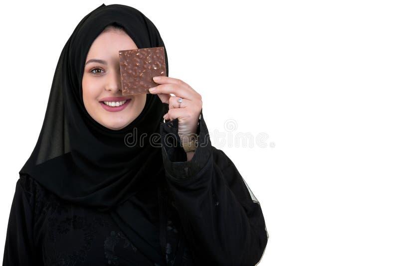Belle femme musulmane de sourire avec le hijab mangeant du chocolat d'isolement sur le fond blanc image libre de droits