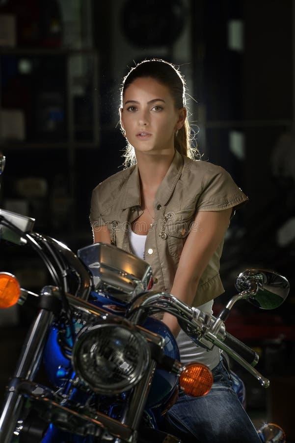 Belle femme mystérieuse dans la lumière se reposant sur sa moto de couperet photo stock