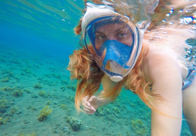 Belle femme nageant sous l'eau Fille rouge de cheveux naviguant au schnorchel dans le masque bleu photographie stock libre de droits