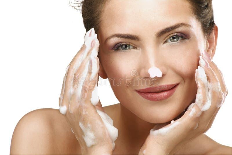 Belle femme nettoyant son visage avec un traitement de mousse images libres de droits