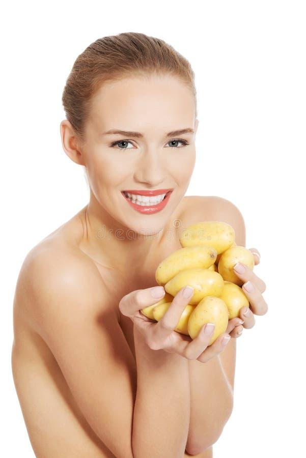 Belle femme nue tenant les pommes de terre crues dans des mains. photos stock