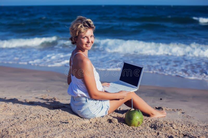 Belle femme occasionnelle avec un ordinateur portable sur la plage avec la mer i image libre de droits